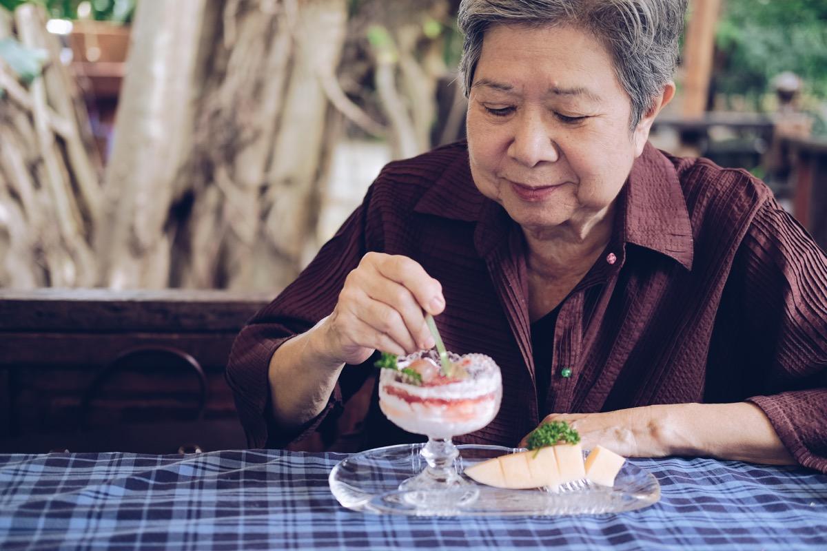 Older woman eating dessert