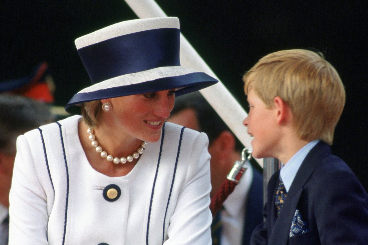 Prince Harry talks to his mother, Diana, Princess of Wales who wears a suit designed by Tomasz Starzewski to VJ Day commemorations