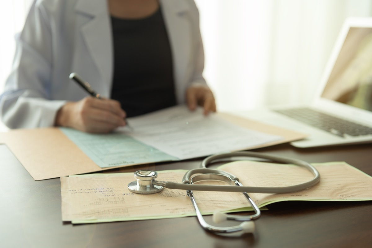 stethoscope and electrocardiogram on medicine report with doctor woman notes information patient medical history at the hospital.