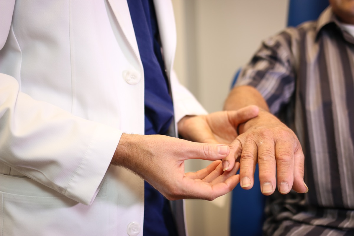 doctor looks at a patient's nails