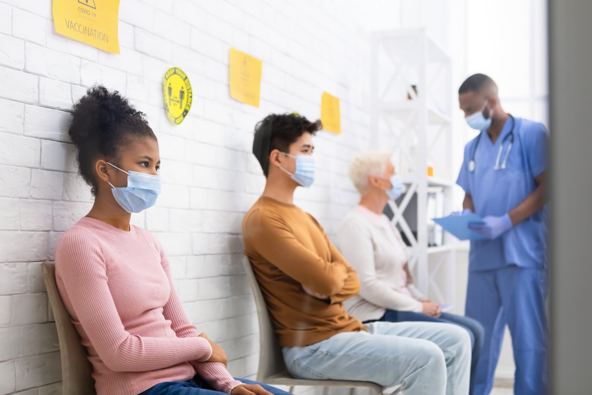 people sitting in doctor's office waiting room wearing masks amid covid