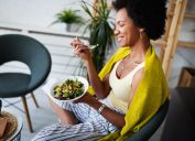 woman, sitting with bowl of salad, eating, smiling