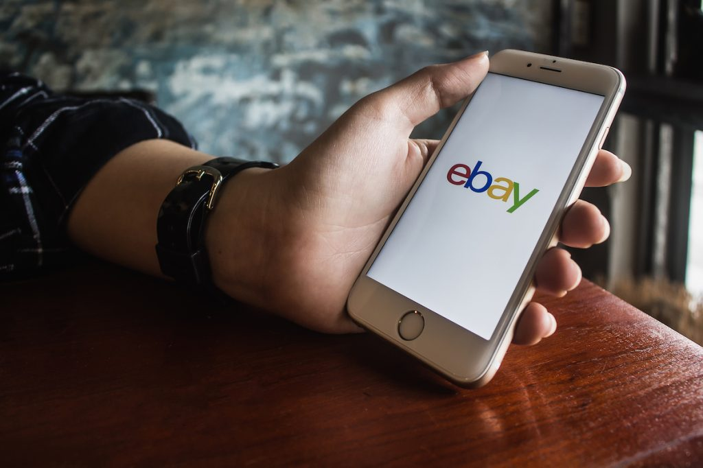 Hand holding iPhone with eBay app on the screen