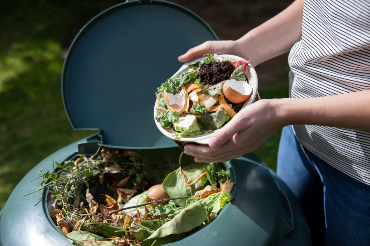woman pouring compost into composter with egg shells on top