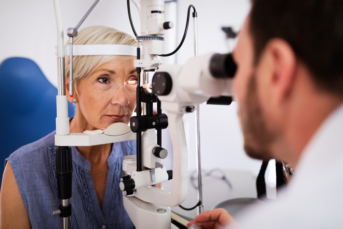woman gets checked by a male eye doctor