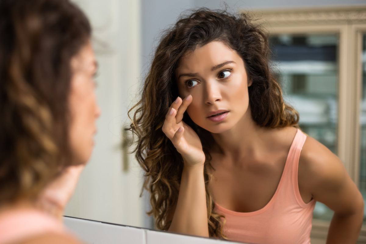 woman looking in a mirror at her eyes