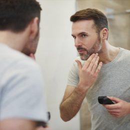 Mature man with electric razor shaving