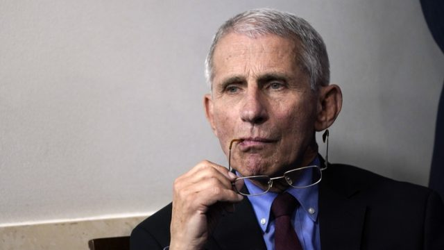 fauci holds his glasses to his face during a covid briefing