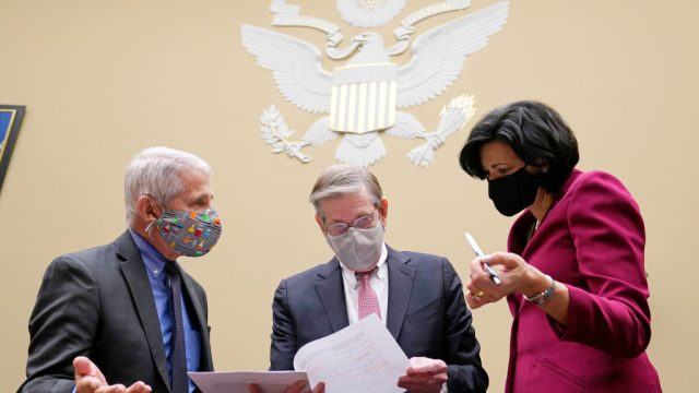 Dr. Anthony Fauci, Dr. David Kessler, and Dr. Rochelle Walensky standing and looking over notes before a senate committee hearing.