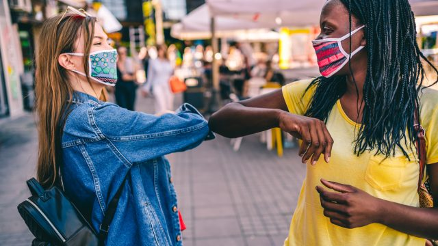 Two young female friends wearing face masks bump elbows to say hello