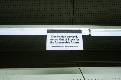 """COVID-19 Coronavirus """"OUT OF STOCK"""" sign on completely empty retail supermarket shopping food and groceries merchandise products display shelves."""