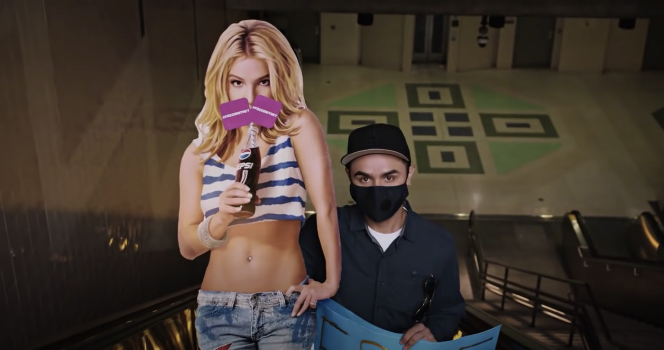 A man wearing a mask sitting next to a cardboard cutout of Britney Spears from the series Framing Britney Spears