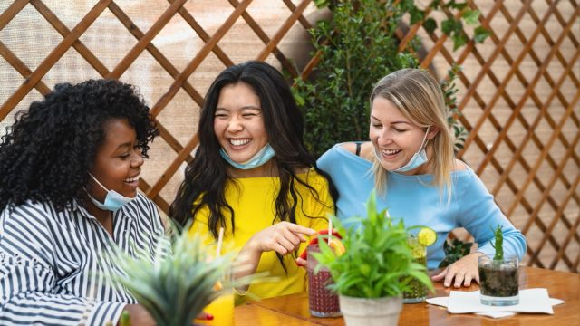 group of three female friends eating lunch with masks down