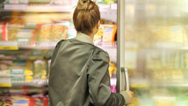 Woman choosing frozen food from a supermarket freezer