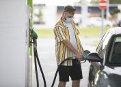 Young Adult Man With Protective Face Mask Refueling Car.
