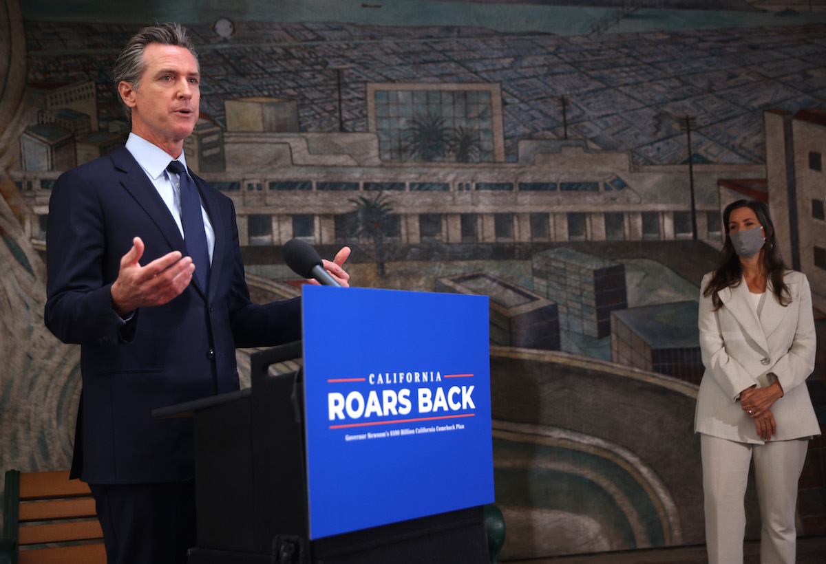 California Gov. Gavin Newsom (L) speaks during a press conference as Oakland Mayor Libby Schaff (R) looks on at The Unity Council on May 10, 2021 in Oakland, California.