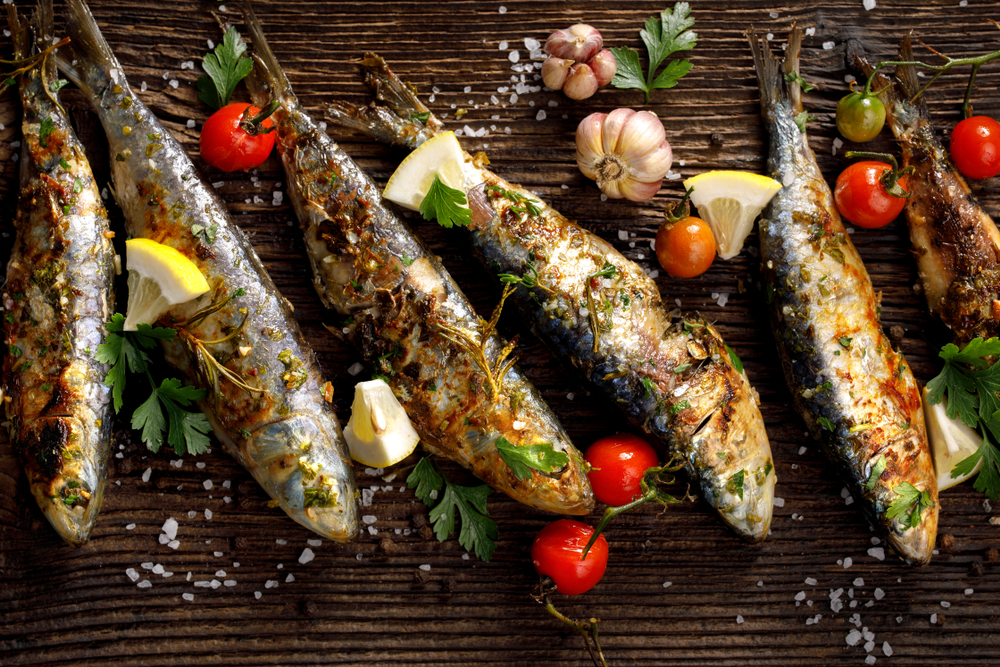 Grilled sardines on a wooden board with tomatoes, lemon, and garlic