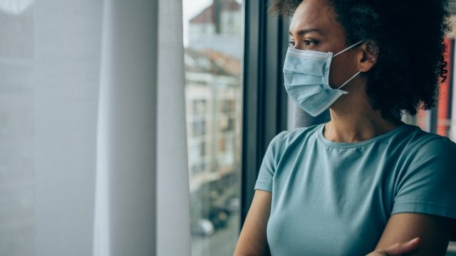 woman wearing protective face mask and looking through window at home during Coronavirus/COVID-19 pandemic.