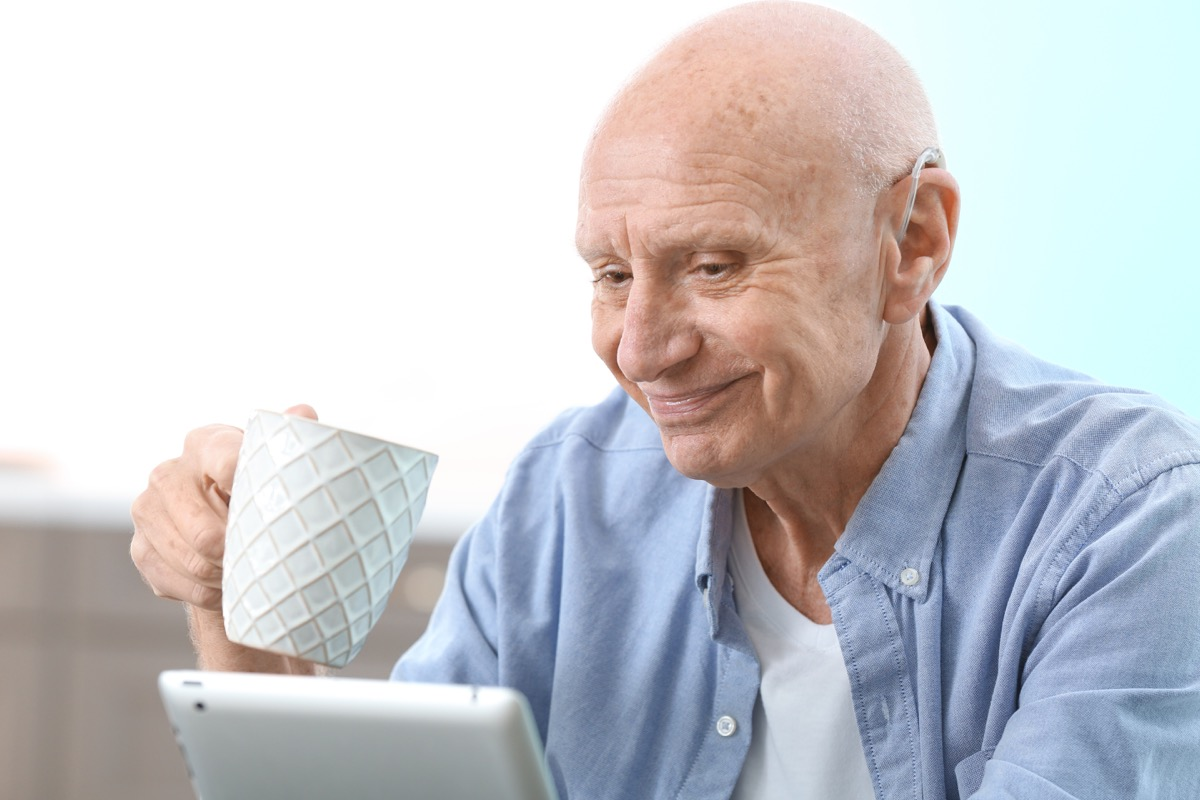 Man wearing hearing aid while on computer