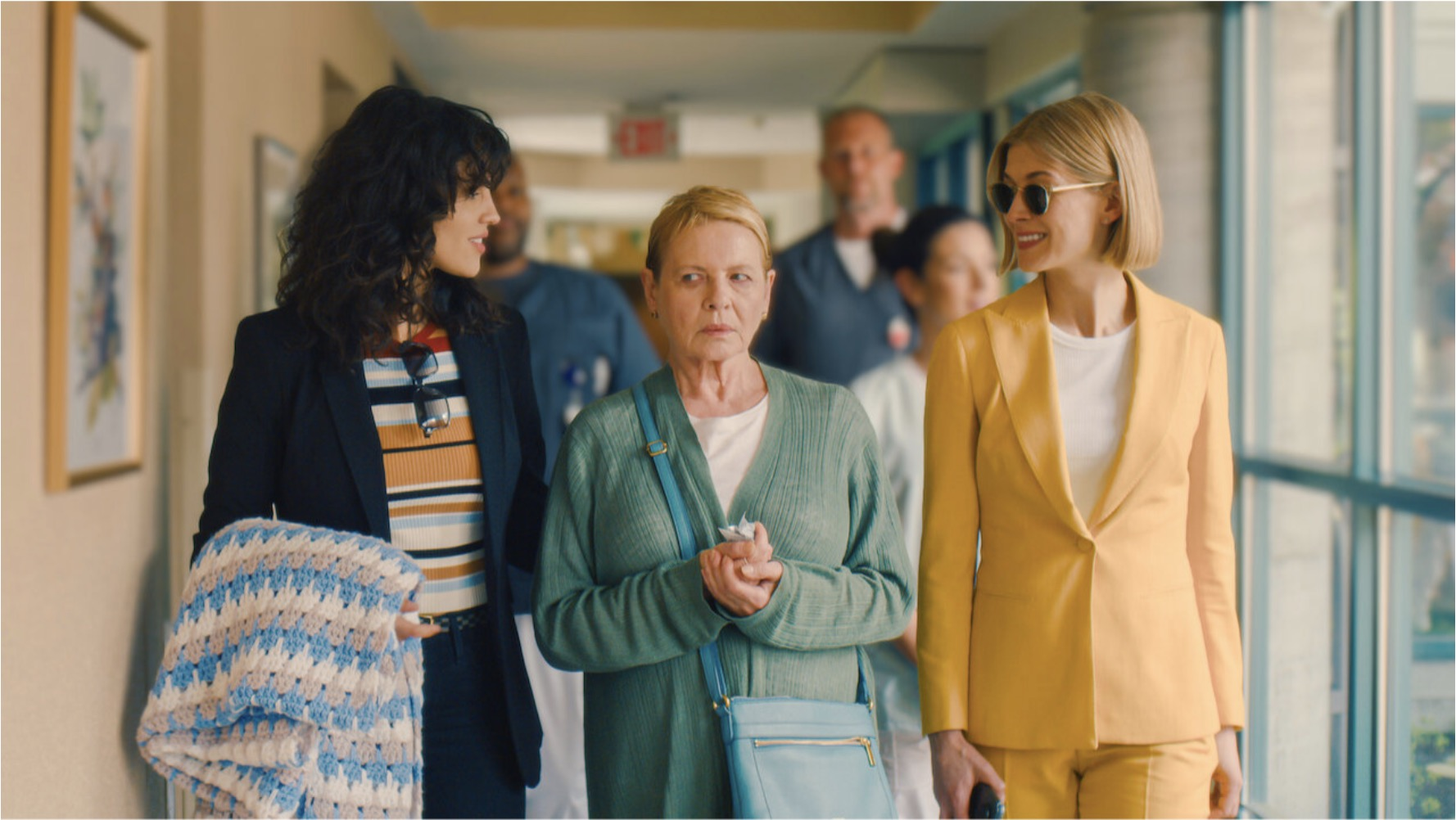 Two younger women walking an older woman down a hallway in a scene from I Care A Lot