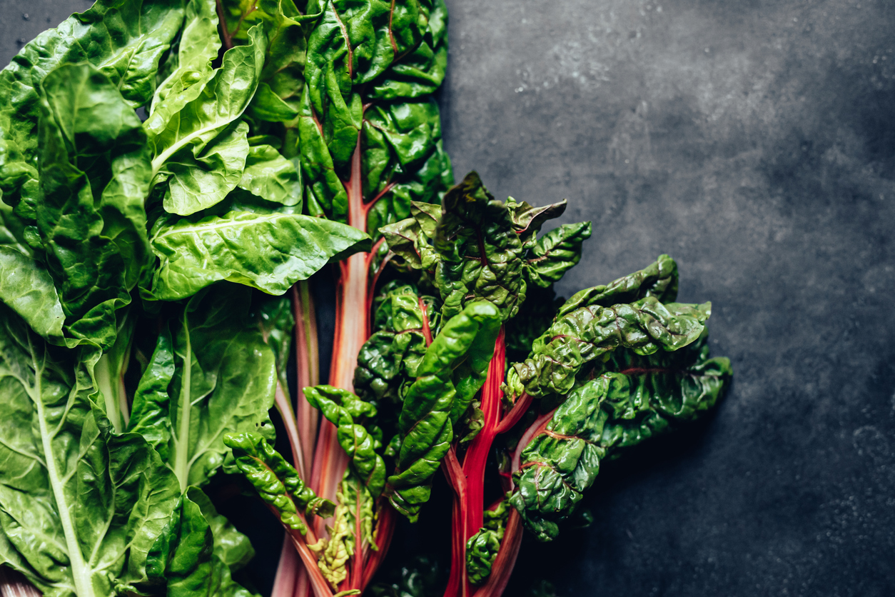 A pile of leafy greens including spinach and chard on a black background