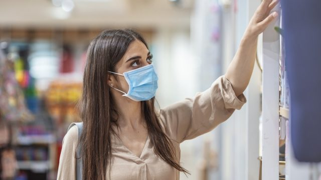 Young woman shopping in a grocery store and wearing protective medical mask. Women with face mask for protection against influenza virus shopping. Shopping in supermarket