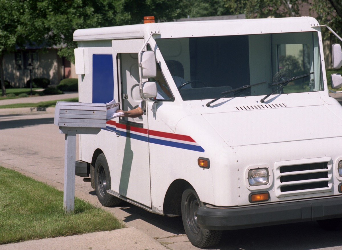 a mail carrier delivers mail, reaches out of the mail truck