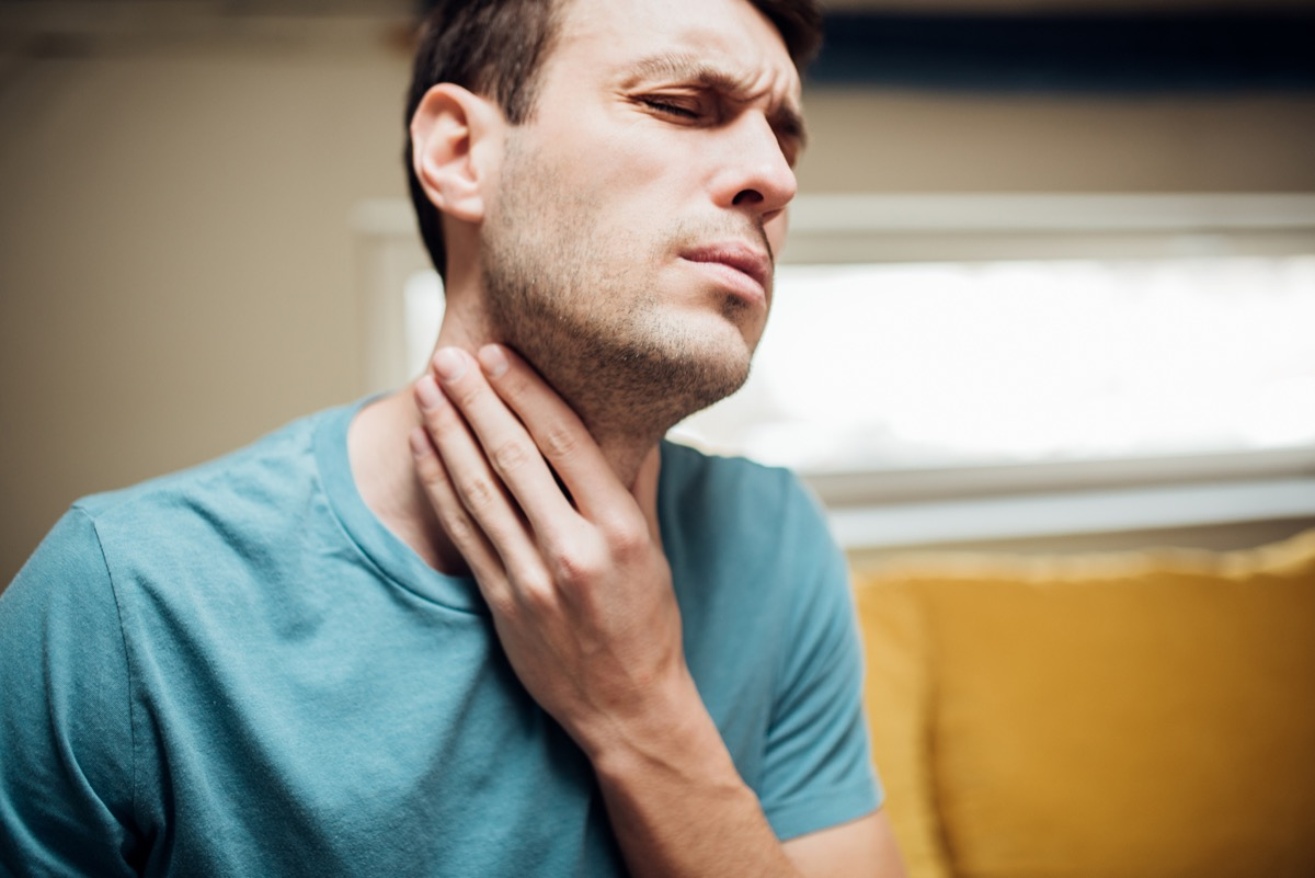 man touching his neck in pain