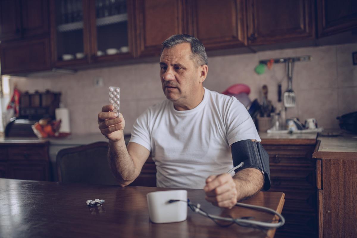 man checking blood pressure with blood pressure medication