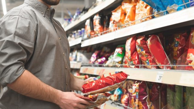 man buying chips in grocery store