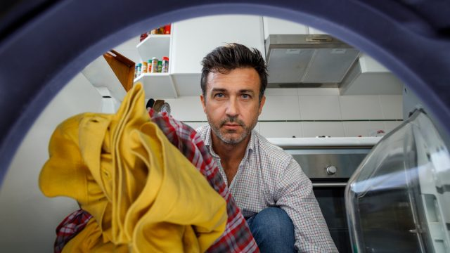 Middle-aged man putting clothes in the washing machine. View from inside.