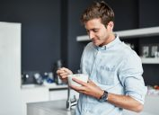 young man eating food out of a bowl