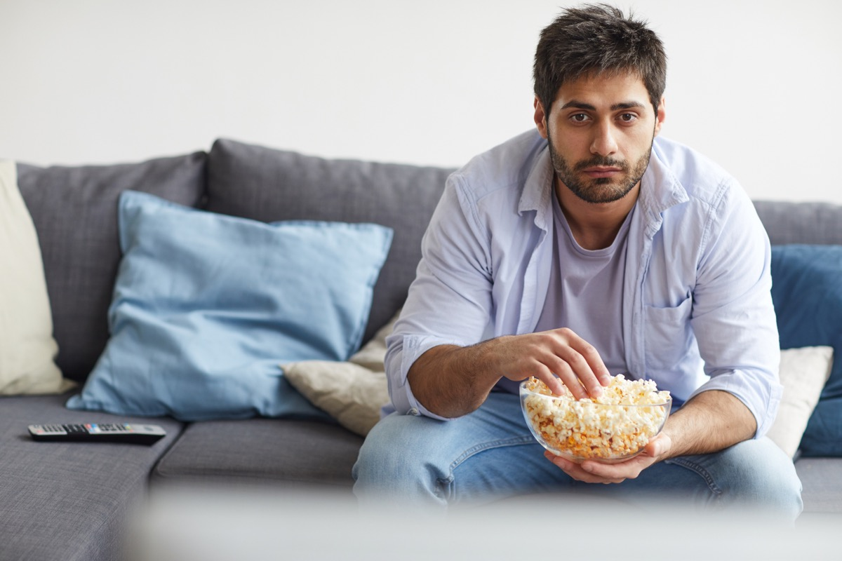 man eating popcorn while watching TV