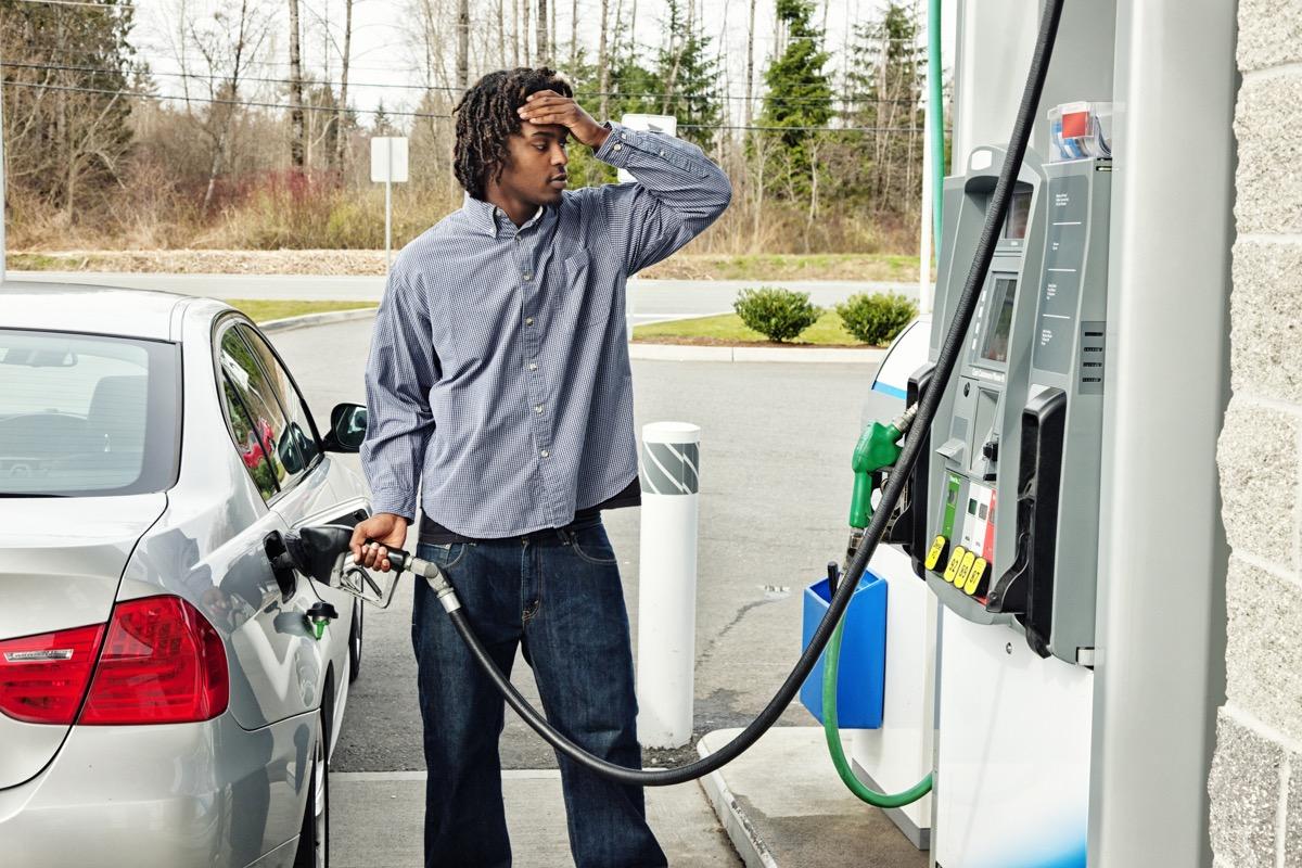 stressed man at gas pump