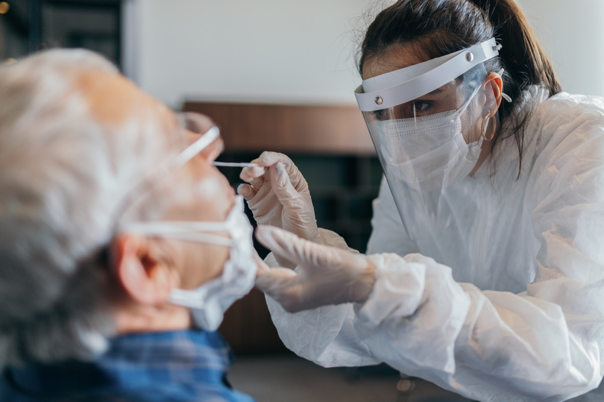 Female doctor in protective suit taking nose swab test from senior man