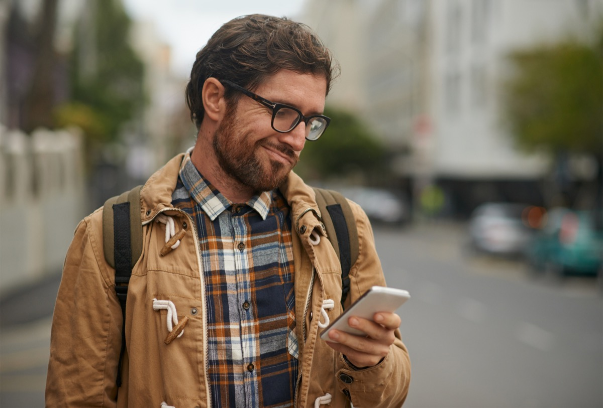 man looking at phone confused in city