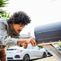 man looking into mailbox in street
