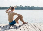 man in swim trunks looking out at lake