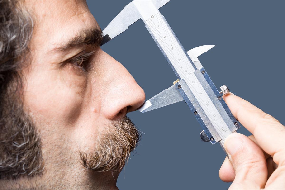 close up of man measuring his nose, big nose