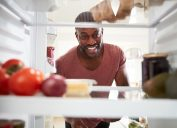 30-something man opening fridge and looking inside