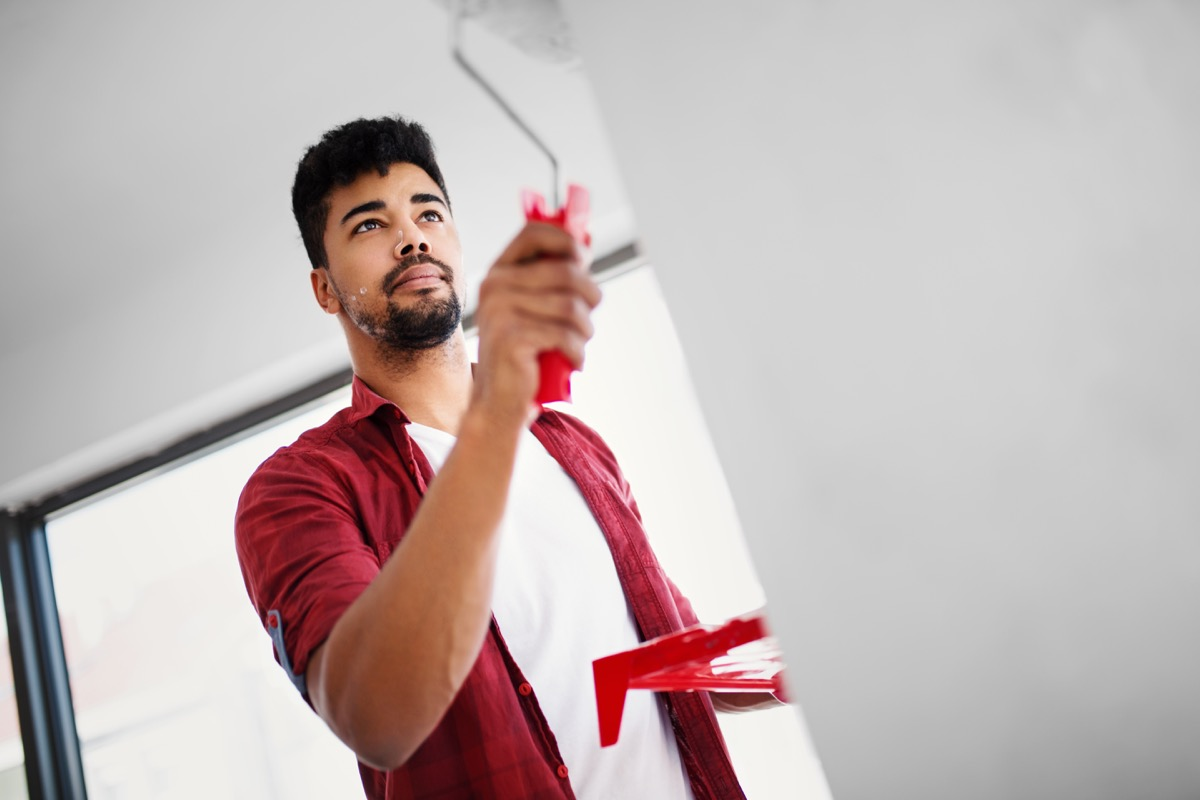 Low angle view of young man painting wall in his apartment.