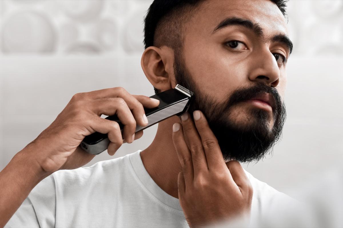 Handsome bearded man shaving his beard