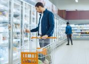 man shopping in the frozen foods section of a supermarket