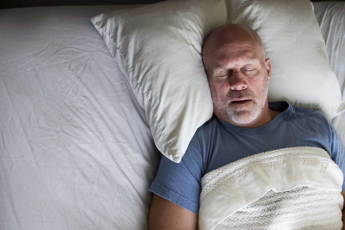 Overhead photo of a man sleeping in a bed.