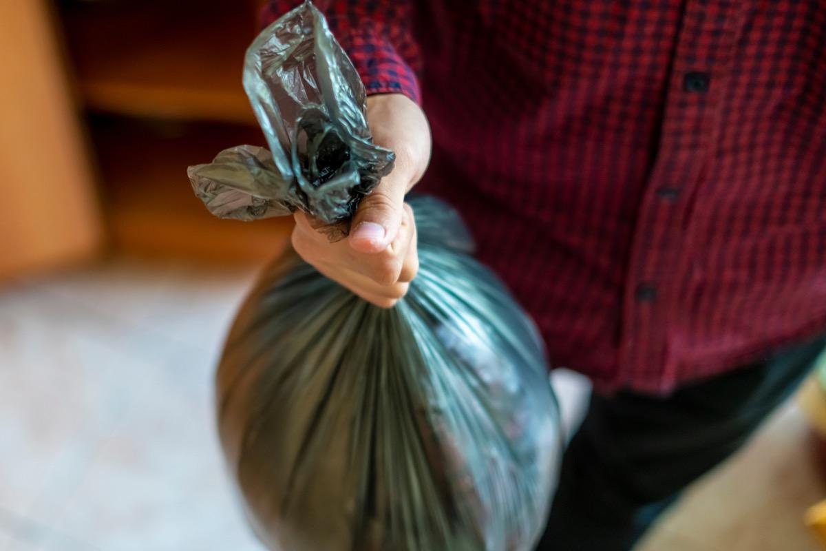 man throwing away black trash back
