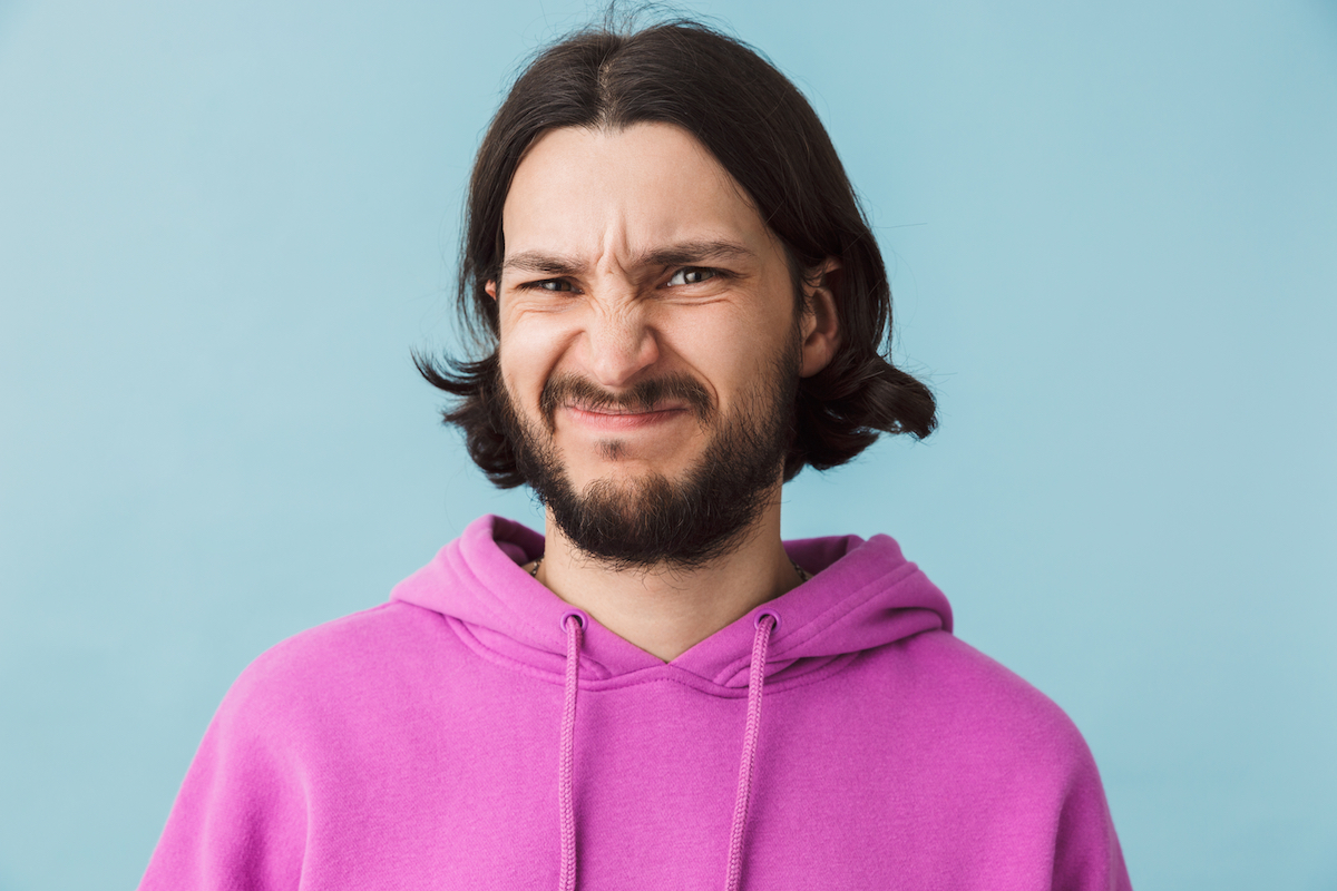 Portrait of a disgusted young bearded man wearing hoodie