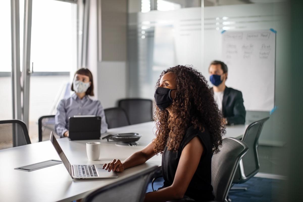people in an office wearing masks