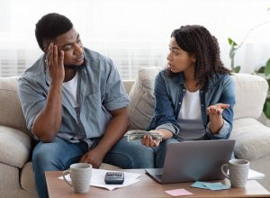 ouple accounting family budget at home, wife scolding her husband for overspending and lack of money