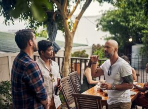 a small group of men talking outside at a party