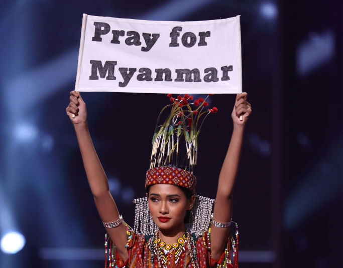 """Miss Myanmar Ma Thuzar Wint Lwin competing in the 2021 Miss Universe pageant while holding up a sign that says """"Pray for Myanmar"""""""